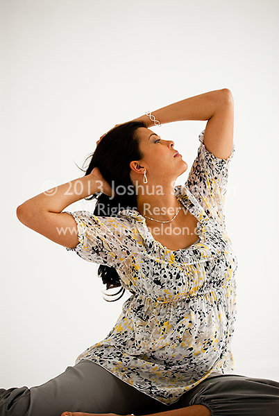 Pregnant Hispanic woman, sitting down, hands in her hair