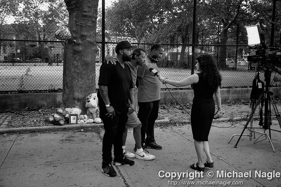BROOKLYN, NY — JULY 13, 2021:  Hannah Kliger, News 12 Brooklyn reporter, right, interviews the great grandfather of 1 year-old Davell Gardner, Jr., who was shot while sitting in his stroller at a barbecue a year ago today, with Stanley, Gardner's godfather, left, and MikeTucker, an anti-gun violence community activist, in front of a memorial at Raymond Bush Playground in Brooklyn, NY on July 13, 2021. Two suspects were charged in May, in what investigators believe to be part of a feud between rival gangs. Photograph by Michael Nagle