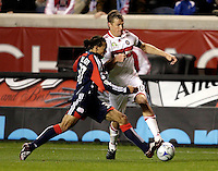 New England midfielder Kevin Alston (30) tries to poke the ball away from Chicago Fire forward Brian McBride (22).  The Chicago Fire tied the New England Revolution 1-1 at Toyota Park in Bridgeview, IL on May 9, 2009.
