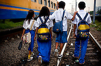 Students of Kartini Emergency School who live along the railway tracks walk to school together. Since the early 1990s, twin sisters Sri Rosyati (known as Rossy) and Sri Irianingsih (known as Rian) have used their family inheritance to set up and run 64 schools in different parts of Indonesia, providing primary education combined with practical skills to some of the country's most deprived children.   .