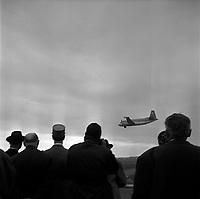 """cérémonie de baptême de l'avion militaire """"Bréguet 1150 Atlantic"""" destiné aux forces de l'OTAN en présence de M. Pierre Mesmer (ministre de la Guerre) et de son épouse (marraine de l'avion),le  3 novembre 1961. aux Ateliers Bréguet (Colomiers)<br /> <br /> Vol de l'avion militaire """"Bréguet 1150 Atlantic"""" piloté par le chef-pilote Bernard Witt : au 1er plan plan taille de dos des personnalités assistant au vol ; en arrière-plan avion en vol (vue de côté)."""