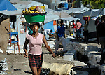 """Carrying bananas on her head, a woman walks through the largest """"tent city"""" of Haitian earthquake survivors, located on a former nine-hole golf course in Port-au-Prince. The Petionville Club is host to more than 44,000 people.."""