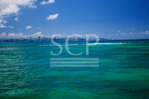 Salvador, Bahia, Brazil. A view of Salvador from the reef around Itaparica Island, in the blue green sea of All Saints Bay.