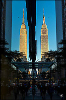 Empire State Building with it's reflection in a window.