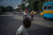 Pedestrians cross the street at a busy intersection in downtown Kolkata, West Bengal, India.
