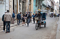 Cuba, Havana.  Street Scene, Old Havana.  Men Talking.  Bicycle Taxi, Bicitaxi.