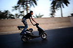 """Baghdad, Iraq  : Fri 15th Oct 2010 :..A young teen performs on his scooter as part of an unofficial bike show  in Baghdad's Jadriya district. An underground youth scene has developed around motorbike culture in the Iraqi capital. .Every week Iraqi teens and young men arrive with their motorcycles, scooters and bicycles at selected street locations to  perform tricks and socialize as part of a burgeoning Baghdadi bike culture. .From """"Yesterday's War, Today's Iraq,"""" an ongoing series documenting Iraq and Iraqis as US forces withdraw from the country and media interest wanes. ."""