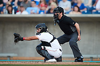 Kannapolis Cannon Ballers catcher Victor Torres sets a target as home plate umpire Billy Cunha looks on during the game against the Charleston RiverDogs at Atrium Health Ballpark on July 4, 2021 in Kannapolis, North Carolina. (Brian Westerholt/Four Seam Images)