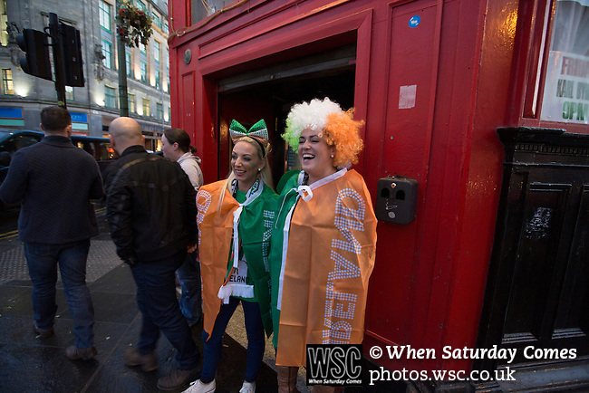 Scotland 1 Republic of Ireland 0, 14/11/2014. Celtic Park, European Championship qualifying. Two Republic of Ireland football fans draped in flags, pictured outside a bar at Glasgow Cross before the European Championship qualifying match against Scotland at the city's Celtic Park. Scotland won the match by one goal to nil, scored by Shaun Maloney 16 minutes from time. The match was watched by 55,000 at Celtic Park, the venue chosen to host the match due to Hampden Park's unavailability following the 2014 Commonwealth Games. Photo by Colin McPherson.
