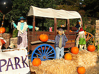 Haybales, pumpkins, a covered wagon and 'stuffed' folks.  Maybe they're getting ready for a hayride.  A Halloween display welcoming all at the entrance to a kid's park.