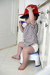 My older son, age two, holds on to both his baseball cap and fire hat while brushing his teeth.