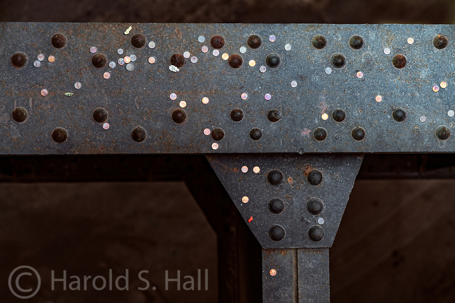 This is a view of metal I-Beams as seen from the High Line Park in New York City.  Count them, there are 50 pennies which people have tossed down.