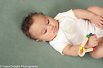 4 month old baby boy closeup on back holding wooden toy rattle in hand