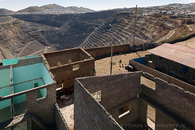 Homes in the Esperanza neighborhood are seen on the very edge of the open-pit mine in Cerro de Pasco, on June 28, 2013. Most of the homes in the area have already been bought by the mining company to expand the pit, but a few residents have held against the pressure to sell.