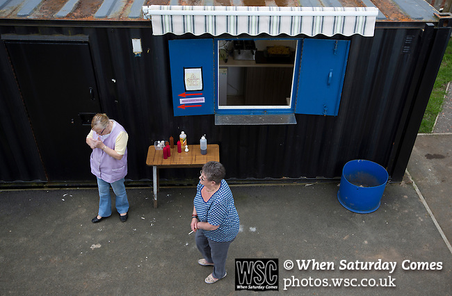 Cefn Druids AFC 1 Buckley Town 0, 12/04/2014. The Rock, Cymru Alliance league. Two refreshment hut staff take a cigarette break at The Rock, Rhosymedre, home to Cefn Druids AFC, prior to the club's final home game of the season against Buckley Town in the Cymru Alliance league. Druids, reputedly the oldest football club in Wales, won the Alliance league the previous week and were awarded the trophy after the Buckley Town match, which they won by 1 goal to nil, watched by a crowd of 246. The Cymru Alliance was the second tier of Welsh football based in north and mid Wales, promotion from which led directly into the Welsh Premier League. Photo by Colin McPherson.