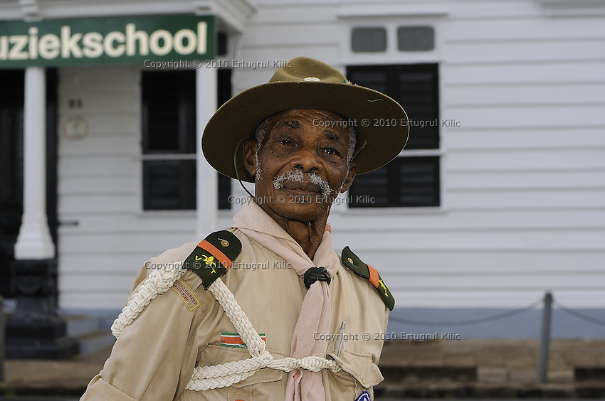 An elder scout commander stands as attendant of the ceremonies at ST. Petrus and Paulus Cathedral and poses at front of National Music School of Suriname.....Blessing and First Worship of ST. Petrus and Paulus Cathedral (AKA World's largest wooden cathedral)