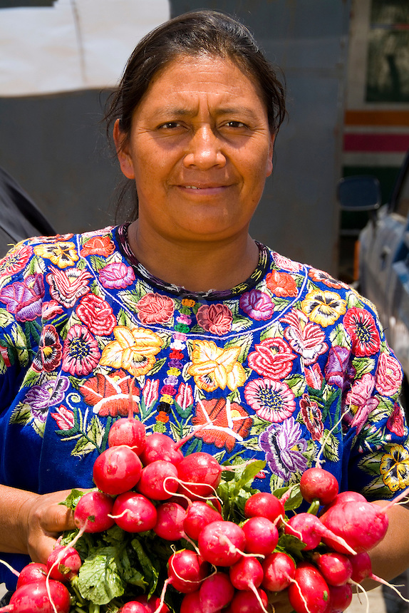 Local colorful woman with red radishes in market with colorful printed dress in tourist village of Antigua Guatemal