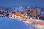 The lights of Ski Time Square glow at dusk in the base area of the Steamboat ski resort.