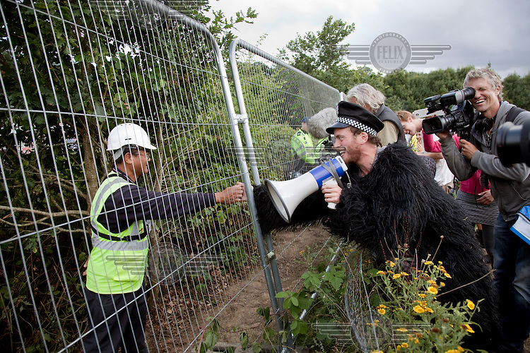 A demonstrator dressed in a gorilla suit and wearing a policeman's cap reaches across the perimeter fence around the Cuadrillia drilling site in Balcombe, West Sussex to shake hands with a private security guard during an anti fracking demonstration. The protesters at Balcombe in West Sussex are worried about the environmental effects of hydraulic fracturing (or fracking) which involves injecting a mixture of water, chemicals and sand into shale rock in order to extract oil and gas trapped below ground. They have been joined by anti fracking demonstrators from across the UK and Ireland. The energy company Cuadrilla is prospecting for oil and gas in West Sussex and the protesters are keen for the company to stop its operations to preserve the natural environment.