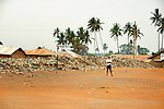 A dirt soccer field backed by a town trash dump near Likoni, Kenya