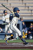 Michigan Wolverines outfielder Clark Elliott (15) follows through on his swing during the NCAA baseball game against the Illinois Fighting Illini at Fisher Stadium on March 19, 2021 in Ann Arbor, Michigan. Illinois won the game 7-4. (Andrew Woolley/Four Seam Images)