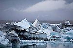 Birds fly over an iceberg, calved off the Breidamerkurjokull glacier, in Jokulsarlon, a glacial lake in Iceland.