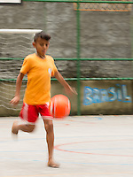 Motion blur of Kids playing football in bare feet at a small pitch in Favela Santo Amaro in the hills around Rio de Janeiro