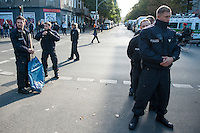 """Bis zu 1.500 Menschen haben am Samstag den 27. September 2014 in Berlin Kreuzberg unter dem Motto """"United Neighbours"""" (Vereinte Nachbarn) gegen Verdraengung sowie das deutsche und europaeische Asylsystem demonstriert. Dabei solidarisierten sie sich nicht nur mit den Fluechtlinge die fuer Asyl und ein Bleiberecht kaempfen, sondern auch mit den von der sog. Cuvry-Brache vertriebenen Menschen und anderen von Zwangsraeumung und Gentrifizierung Betroffenen.<br /> Die Demonstration wurde von einem grossen Polizeiaufgebot begleitet, darunter mehrere Einsatzhunderschaften mit speziellen Festnahme-Einsatzgruppen aus Baden-Wuertemberg.<br /> Im Bild: Polizeibeamte haben ein missliebiges Plakat beschlagnahmt. Was auf dem Plakat stand wollten sie jedoch nicht sagen.<br /> 27.9.2014, Berlin<br /> Copyright: Christian-Ditsch.de<br /> [Inhaltsveraendernde Manipulation des Fotos nur nach ausdruecklicher Genehmigung des Fotografen. Vereinbarungen ueber Abtretung von Persoenlichkeitsrechten/Model Release der abgebildeten Person/Personen liegen nicht vor. NO MODEL RELEASE! Don't publish without copyright Christian-Ditsch.de, Veroeffentlichung nur mit Fotografennennung, sowie gegen Honorar, MwSt. und Beleg. Konto: I N G - D i B a, IBAN DE58500105175400192269, BIC INGDDEFFXXX, Kontakt: post@christian-ditsch.de<br /> Urhebervermerk wird gemaess Paragraph 13 UHG verlangt.]"""