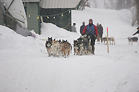 During heavy wind and snow, Brian Mills leaves the Tokotna checkpoint after his 24 hour layover.  2005 Iditarod Trail Sled Dog Race.