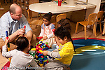 Preschool Headstart 3-5 year olds male play therapist working with student with special needs and other children in the classroom playing with colorful connecting pieces horizontal