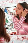 11 year old girl looking at self in mirror adjusting hair vertical