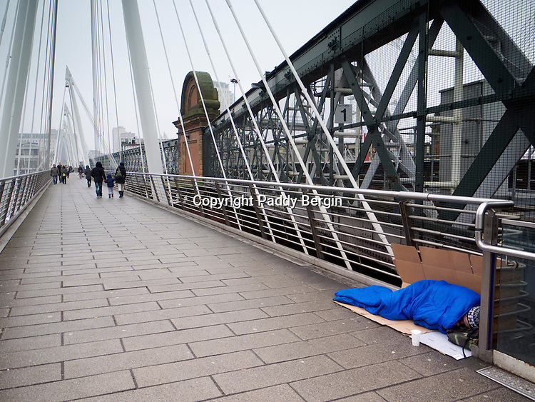 """Homeless person sleeping on Hungerford Bridge in the rain.<br /> <br /> Homelessness is the condition of people without a regular dwelling. People who are homeless are most often unable to acquire and maintain regular, safe, secure, and adequate housing, or lack """"fixed, regular, and adequate night-time residence.""""<br /> <br /> The term homeless may also include people whose primary night-time residence is in a homeless shelter, a warming centre and a domestic violence shelter.<br /> <br /> Stock Photo by Paddy Bergin"""