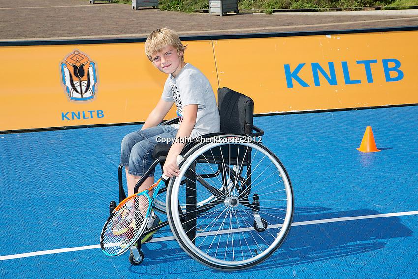 15-09-12, Netherlands, Amsterdam, Tennis, Daviscup Netherlands-Suisse, Boy in wheelchair with tennis racket