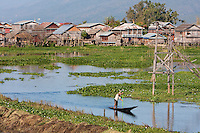 Myanmar, Burma.  Burmese Man Paddles his Canoe through Village Waterway, Inle Lake, Shan State.  Note power lines carrying electricity to village houses.