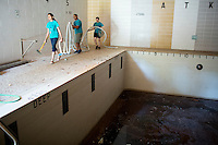 """Members remove hoses and trash from a pool area during """"Circle the City with Service,"""" the Kiwanis Circle K International's 2015 Large Scale Service Project, on Wednesday, June 24, 2015, at the Friendship Westside Center for Excellence in Indianapolis. (Photo by James Brosher)"""