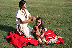 A Native American Indian woman braiding a childs hair