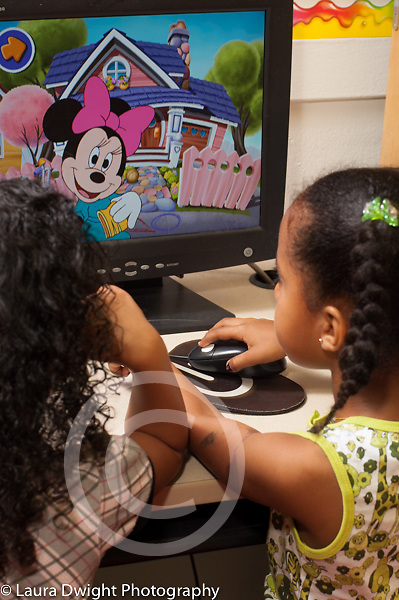 Preschool 4-5 year olds two girls playing at desktop computer in classroom