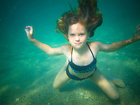 A young girl holds her breath as she floats underwater at Mahai'ula Beach, Big Island.