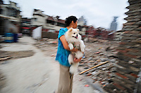 Woman carrying her pet dog across an old neighbourhood, now cleared for development in the old Chinese city.