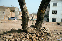 Uighurs walk among the debris of a demolished area of the old town in Kashgar, Xinjiang, China.  If government plans are followed, the old style housing will be replaced by highrise apartment buildings as seen throughout the rest of China.