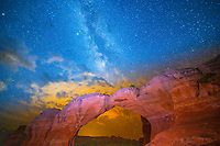 MIlky Way amd clouds lit by Moab, Utah, Broken Arch, Arches National Park,