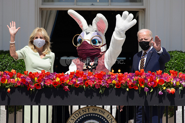US President Joe Biden (R) waves beside First Lady Jill Biden (L) and the Easter bunny (C) while delivering remarks regarding Easter, on the Truman Balcony at the South Lawn of the White House, in Washington, DC, USA, 05 April 2021. The traditional Easter Egg Roll at the White House with thousands of visitors was not held due to the coronavirus COVID-19 pandemic.<br /> Credit: Michael Reynolds / Pool via CNP /MediaPunch