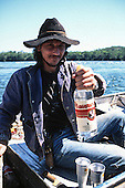 Pantanal, Mato Grosso State, Brazil. Local fisherman in his boat holding a bottle of cachaca, wearing a broad-rimmed hat and with a pistol in a holster on his belt