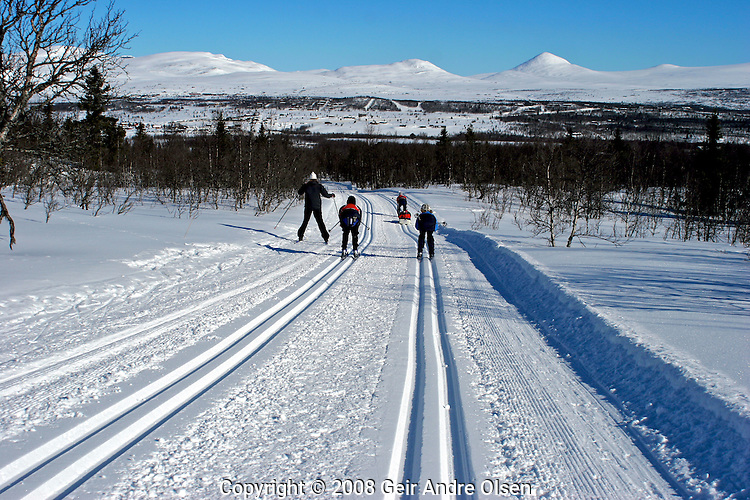 Family skiing at Venabygdsfjellet in the Norwegian mountains, Mt. Muen in the background