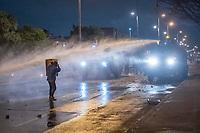 BOGOTA - COLOMBIA, 25-05-2021: Un manifestante se protege del chorro de agua lanzado por una tanqueta del ESMAD (Escuadrón Móvil Antidisturbios de la Policía) durante los disturbios en el sector de las Américas de la ciudad de Bogotá durante el día 28 del Paro Nacional en Colombia hoy, 25 de mayo de 2021, para protestar contra el gobierno de Ivan Duque además de la precaria situación social y económica que vive Colombia. El paro fue convocado por sindicatos, organizaciones sociales, estudiantes y la oposición. / A protester protects himself from the jet of water launched by an ESMAD tank (Police Anti-Riot Mobile Squad) during the riots at Portal Las Americas sector of the city of Bogota during the day 28 of the National strike in Colombia today, May 25, 2021, to protest against the government of Ivan Duque in addition to the precarious social and economic situation that Colombia is experiencing. The strike was called by unions, social organizations, students and the opposition in Colombia. Photo: VizzorImage / Diego Cuevas / Cont