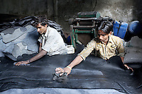 Two young men work with leather in a tannery workshop in the Jajmau area of Kanpur.