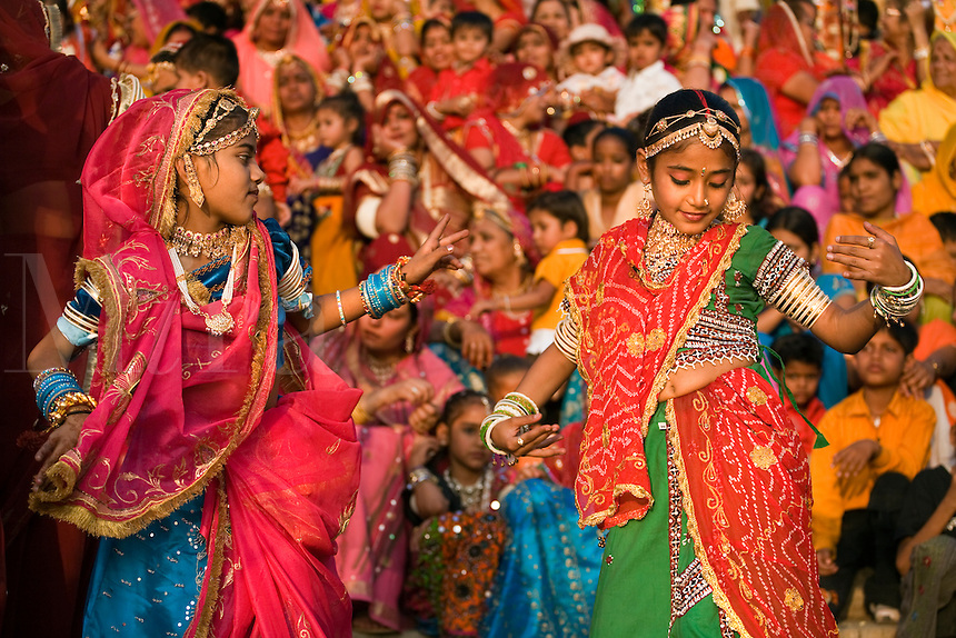 Rajasthani girls dressed in their finest dances at the GANGUR FESTIVAL also known as the MEWAR FESTIVAL - UDAIPUR, RAJASTHAN, INDIA