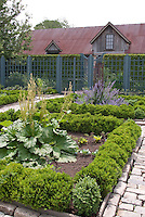 Upscale vegetable garden with cut stone walkway, fence, trellised apple fruit trees and beautiful old barn and fence