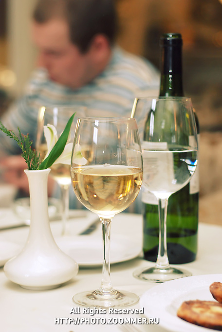 Green bottle of wine and two glasses with champagne and water on table in restaurant