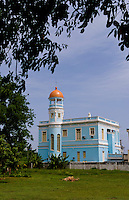 Beautiful blue building hotel from private home along the Malacon in Cienfuegos Cuba with horse drawn carriages